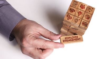 Man holding Employee Engagement building block