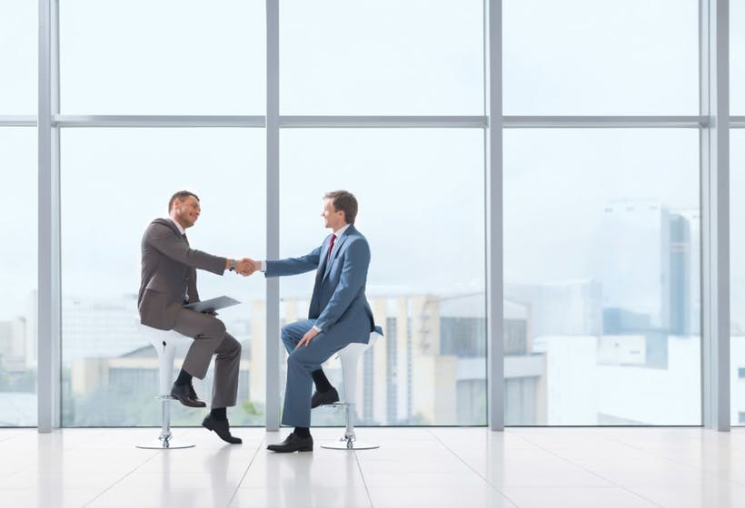 Two business man in suit shaking hands on the work office.