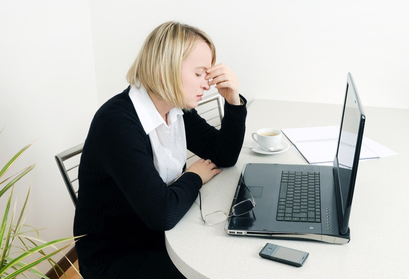 Woman sitting on a desk worrying about Painful Performance Appraisals