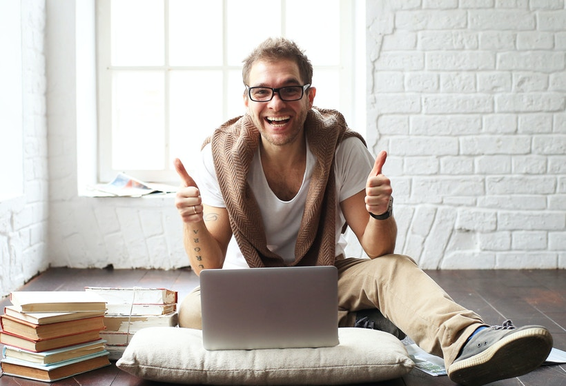 Young man smiling in front of the laptop.
