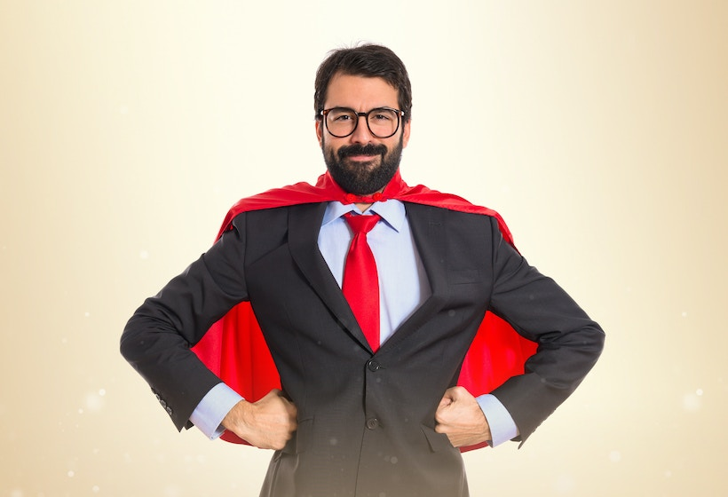 A male Businessman dressed in costume with a superhero red cape.