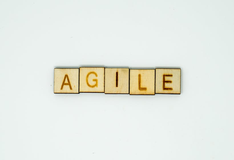 The Word Agile spelled out in wooden blocks. Discussing Agile Performance Management.