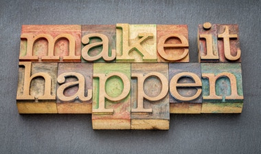 Wooden blocks on a dark table with the words 'make it happen'