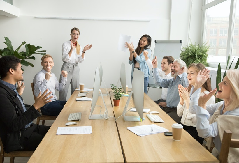 People in a meeting clapping hands.