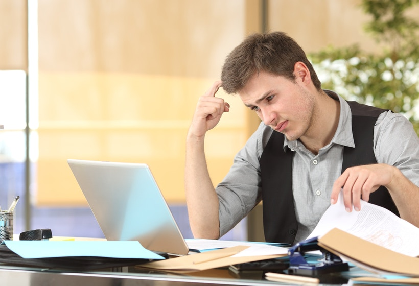 Incompetent employee thinking how to do his job online with messy desk at office.