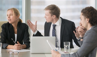 Furious boss scolding young frustrated interns.