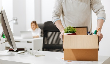 A man filling a box with his office stuff.