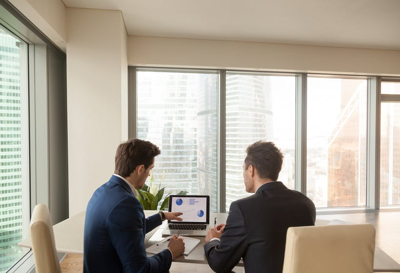 Two men discussing company growth, looking at rising graph on laptop screen, using easy accounting software for small business, stock traders analyzing market, pointing at charts on monitor. Rear view.