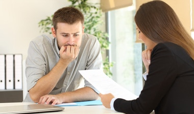 Nervous man looking how the interviewer is reading his resume during a job interview.