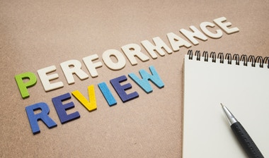 Performance reviews letters on an office desk.